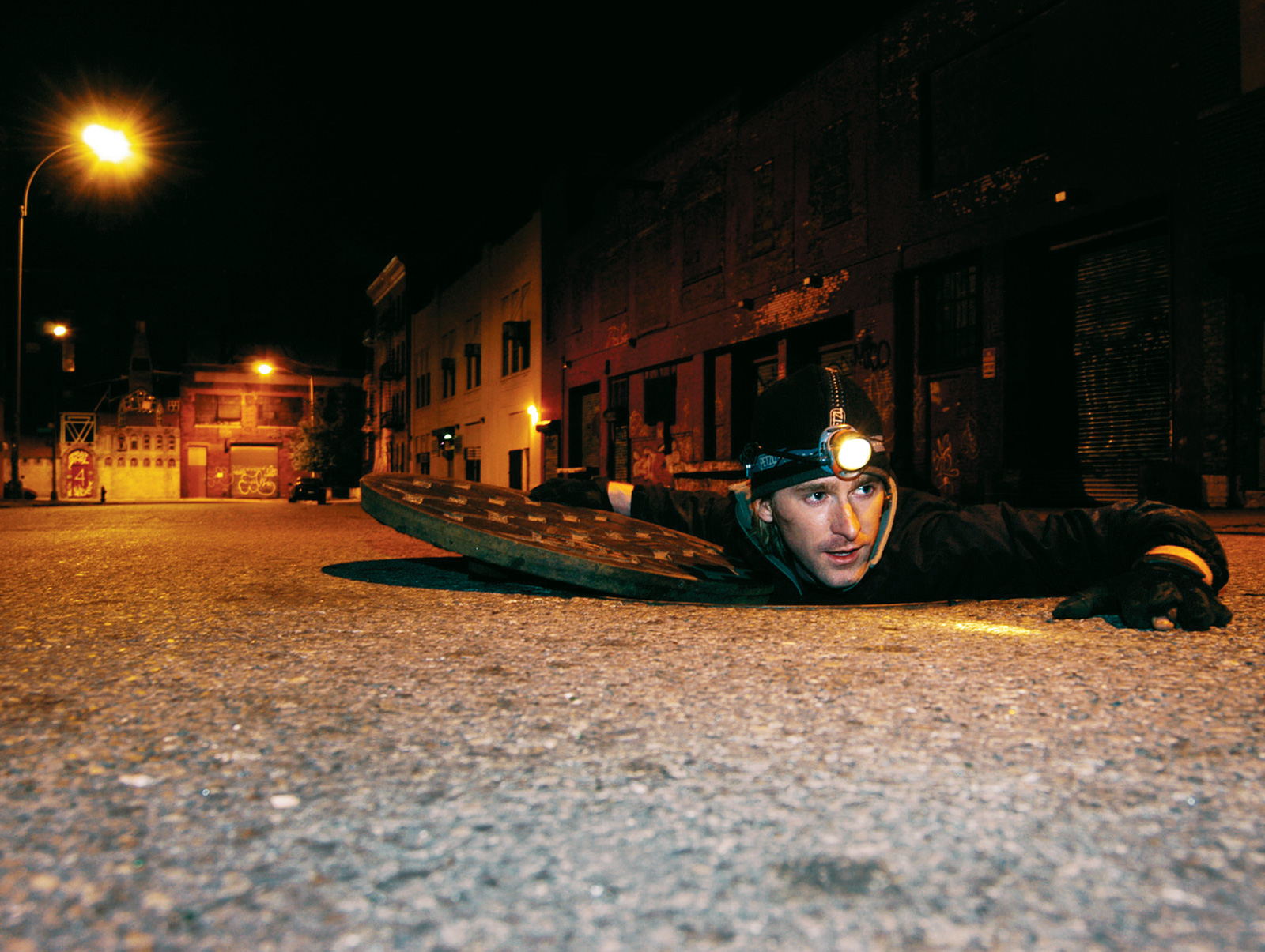 Photographer Steve Duncan crawling out of a man hole