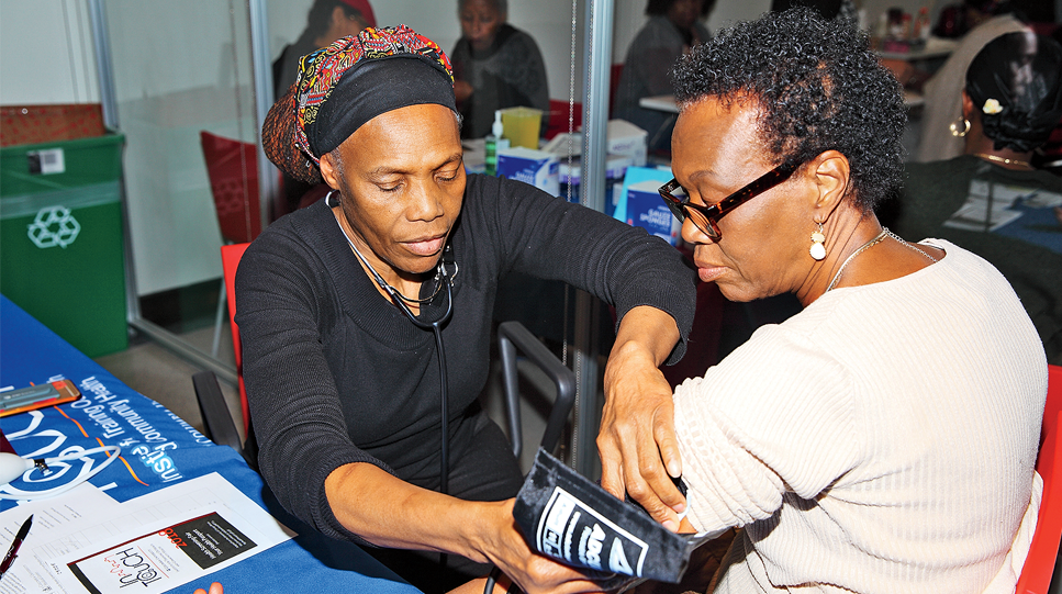 A health worker at Columbia's Community Wellness Center takes a patient's blood pressure
