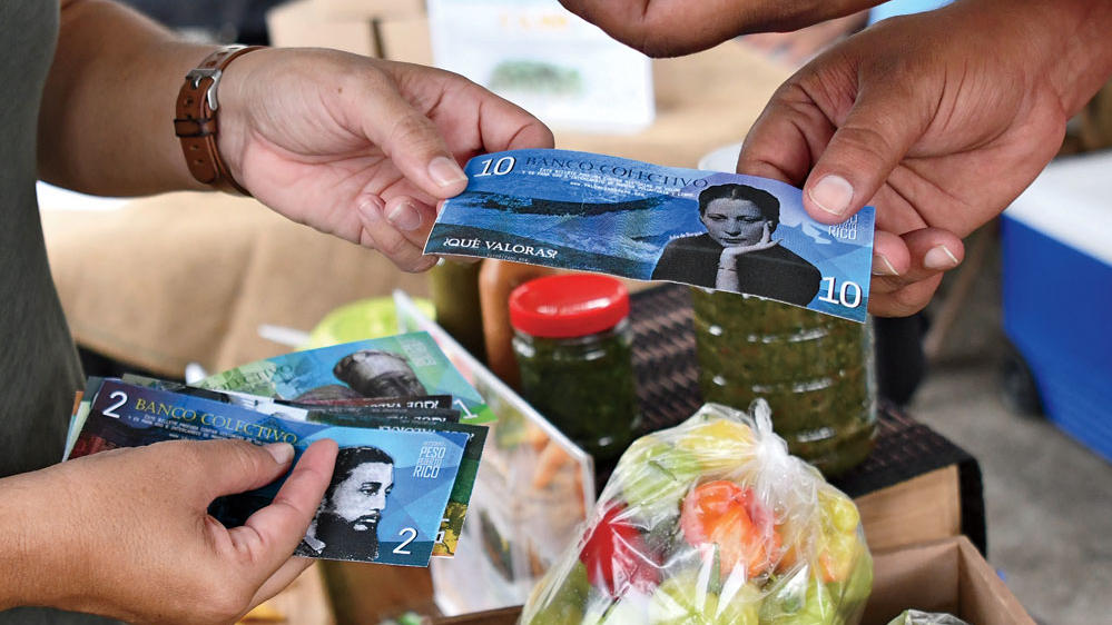 "People exchanging ""Pesos of Puerto Rico"" as part of Columbia professor Frances Negrón-Muntaner's ""Valor y Cambio"" project"