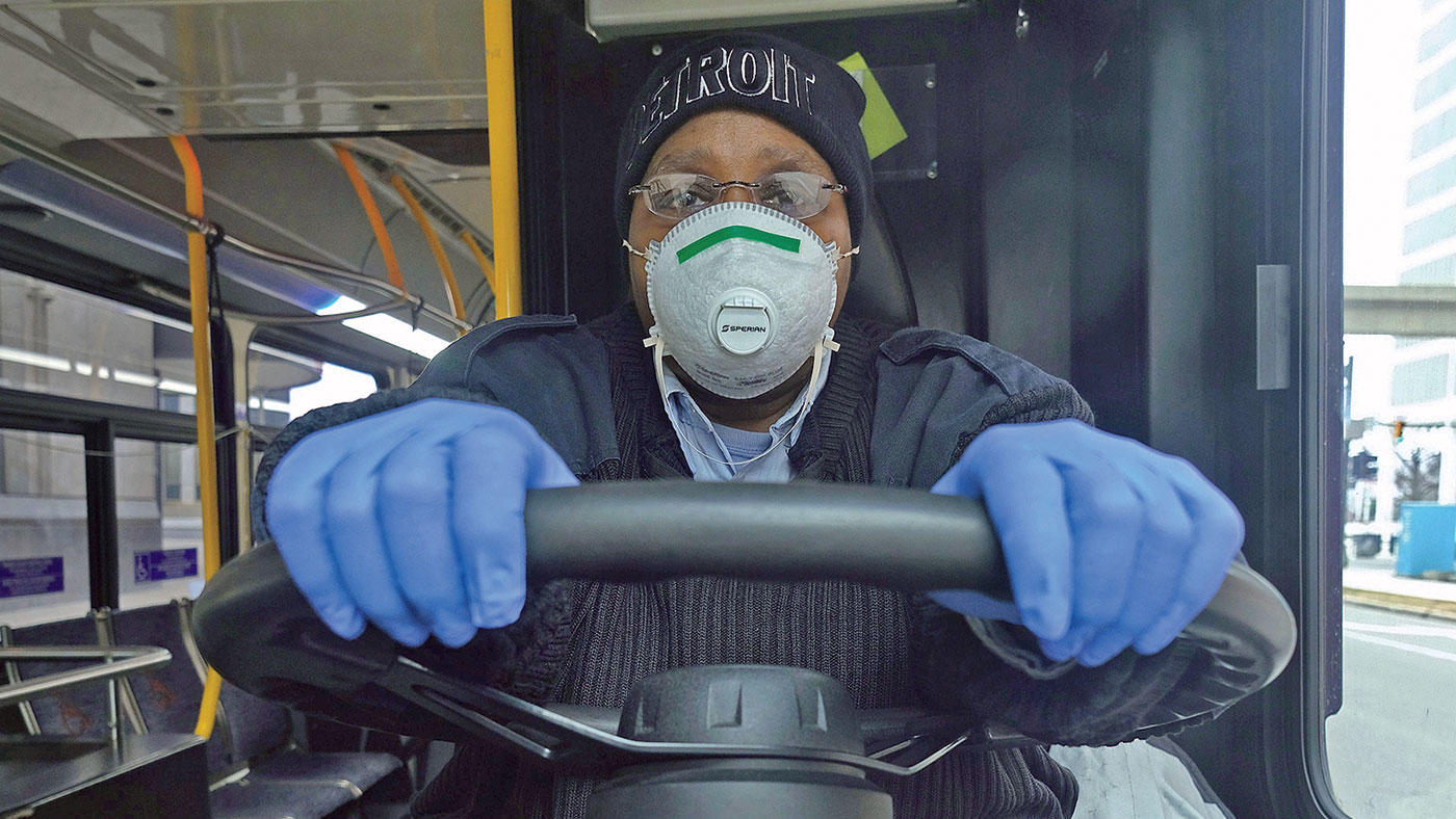 A city bus driver in Detroit wearing a face mask