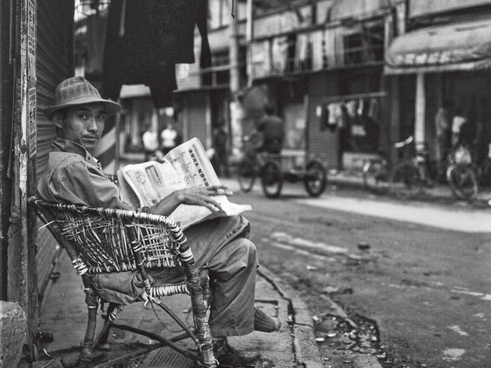Photo of man reading newspaper on street in Shanghai, by Howard French