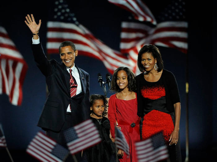 Barack Obama with family in front of American flags