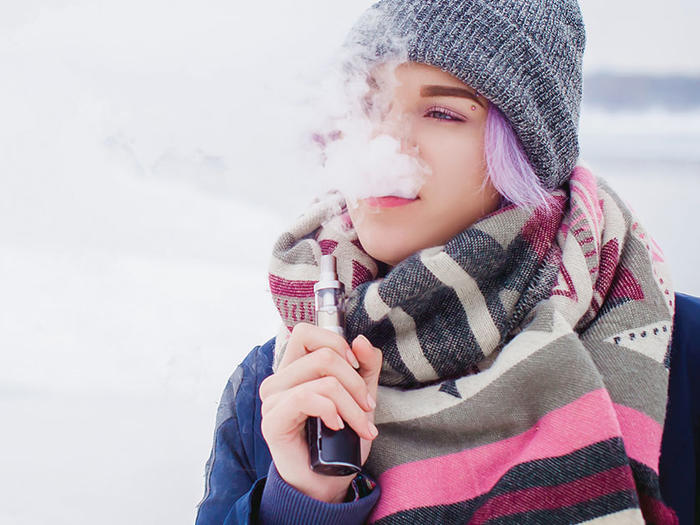 Young woman with purple hair and winter attire vaping with an electronic cigarette