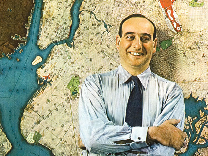 Young Robert Moses standing in front of a map of New York City
