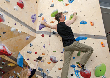 Columbia neuroscientist Mark Churchland on the climbing wall at the Jerome L. Greene Science Center