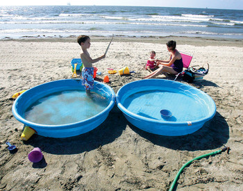Gulf Coast resident Bridget Hargrove and her family wade in pools away from contaminated ocean water in Grand Islae, La., on May 21. (Reuters / Sean Gardner)