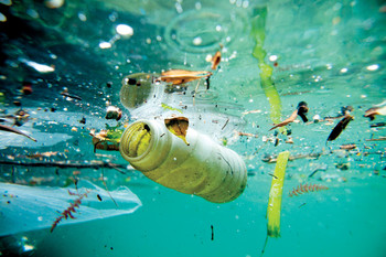 Underwater photo of plastic bottle and other trash floating in ocean