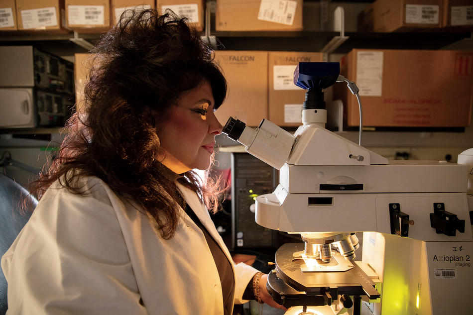 Geneticist Angela Christiano looking through a microscope in her research lab at Columbia University Irving Medical Center