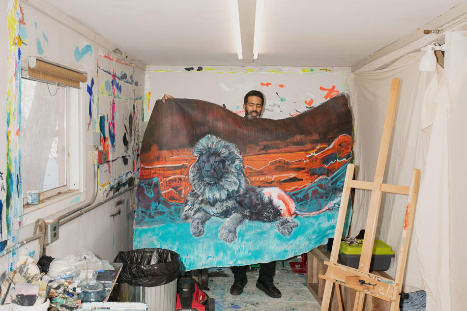Cy Gavin in his studio holding up his painting of a lion