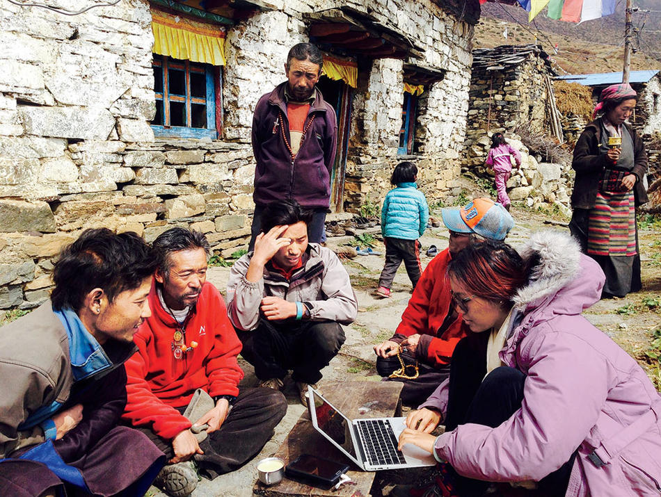 Tsechu Dolma surveys a group of Tibetan refugees in Nepal as part of her work with the Mountain Resiliency Project