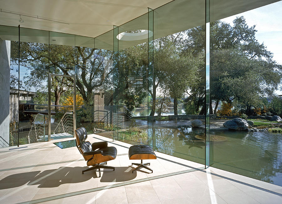 Photo of an Eames lounge chair in a room with glass walls, facing nature