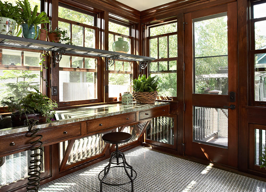 A desk in a sunroom with plants