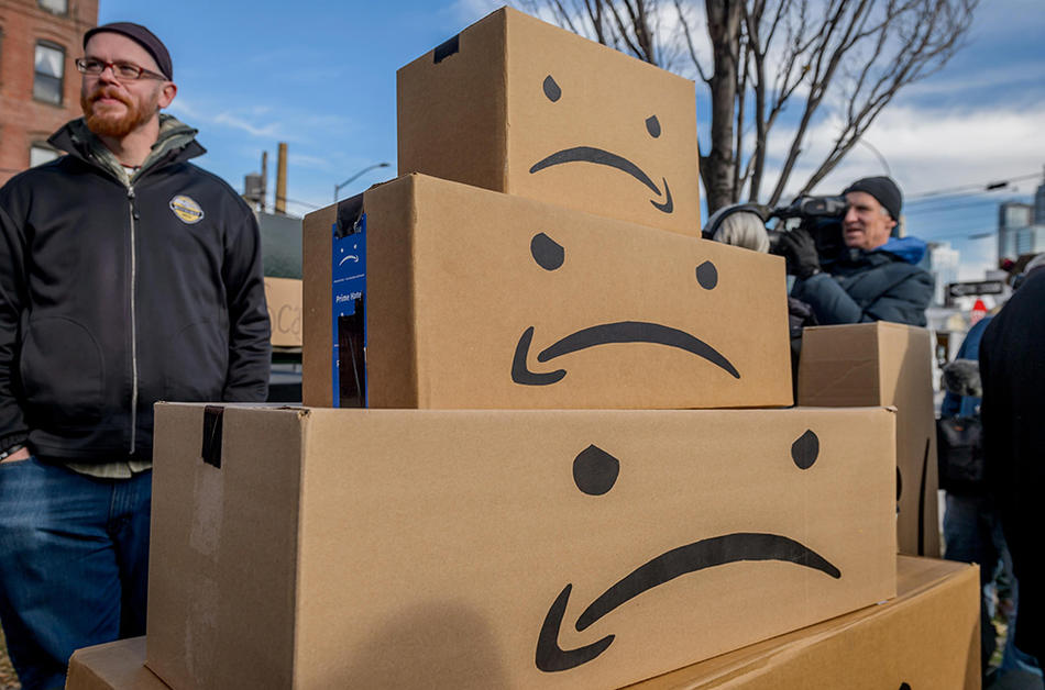 People protesting Amazon's plan to open headquarters in NYC in 2018. Amazon logo is made into sad faces on shipping boxes.