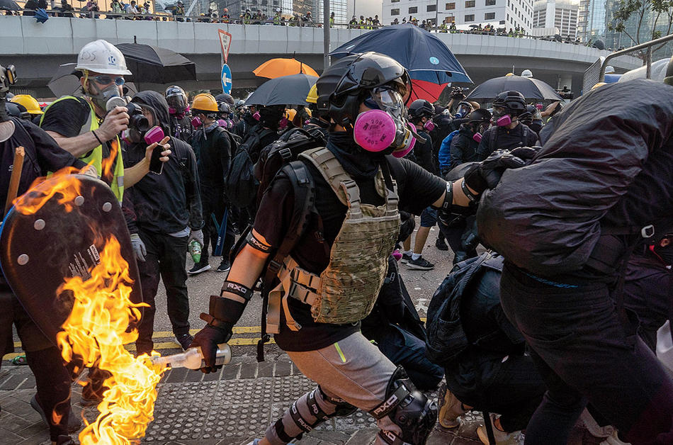 Hong Kong: An anti-government protester throws a Molotov cocktail at riot police. Photograph by Bing Guan, fall 2019