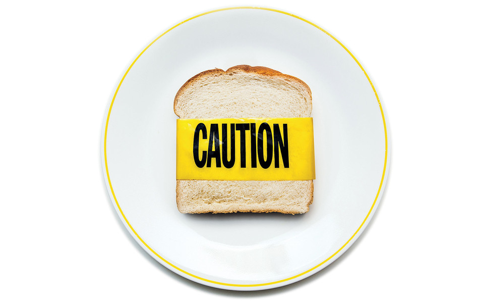 A piece of bread with caution tape to illustrate gluten sensitivity
